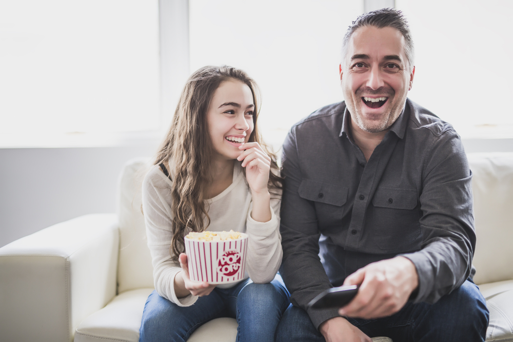 a dad and his daughter watching a movie