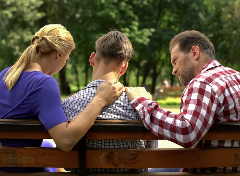 parents and teen boy talking in a park